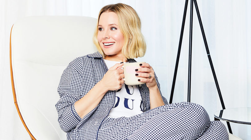 Kristen Bell sitting in pajamas on an armchair holding a mug