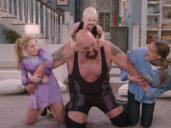 Dad in a wrestling suit play wrestles with his family in the living room