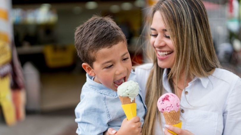 Mother and son eat ice cream together.