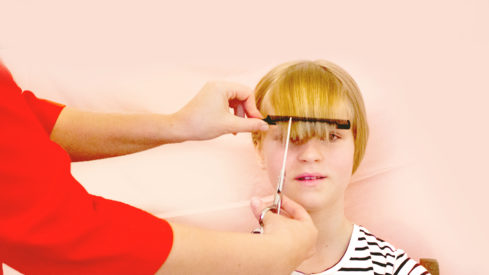 mother illustrating on her daughter how to cut bangs