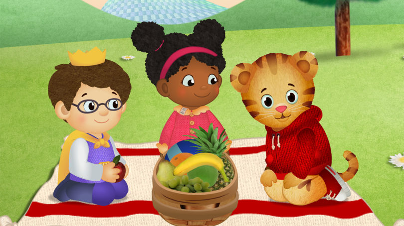 Still from Daniel Tiger's Neighbourhood showing two animated kids and an animated tiger having a picnic in the park