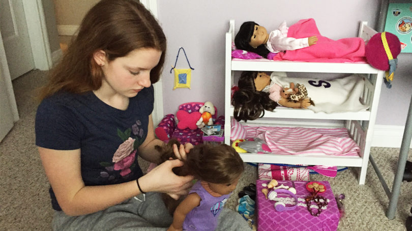 Young teen playing with doll collection
