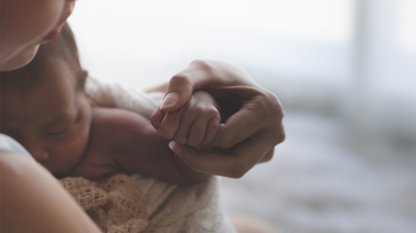 mother holding her newborn who is holding her finger