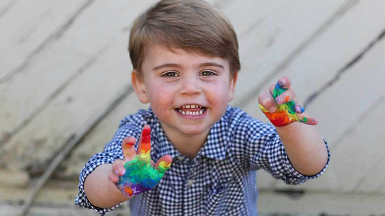 Prince Louis holding out his hands covered in rainbow paint