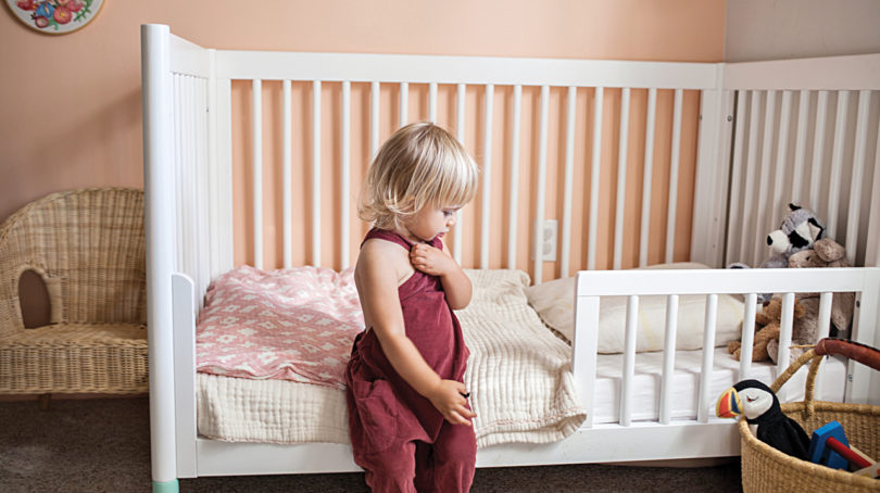 Toddler standing next to bed