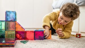 little boy playing with magnetic tiles