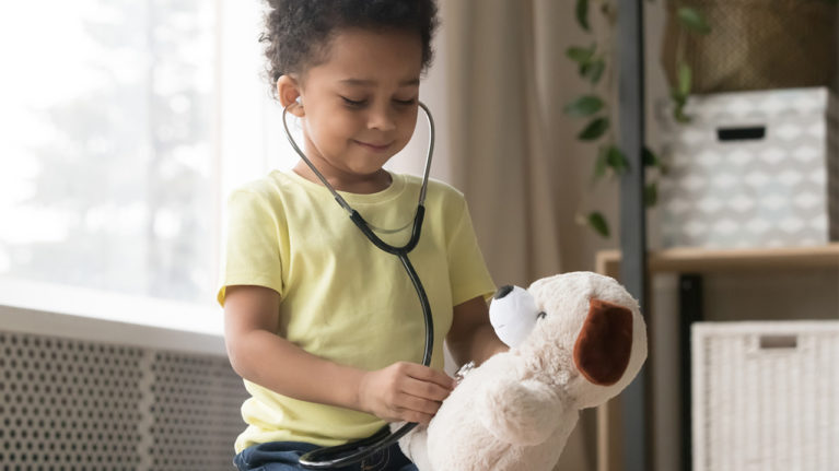 Little kid playing doctor with a stuffed animal