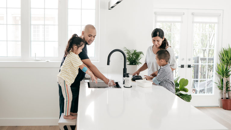 Family of four around the kitchen counter, washing hands
