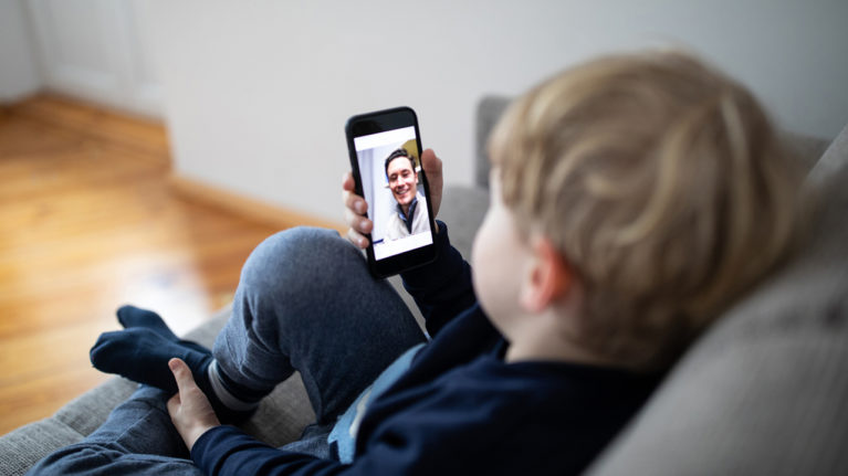 little kid sitting on a couch video chatting on a smartphone