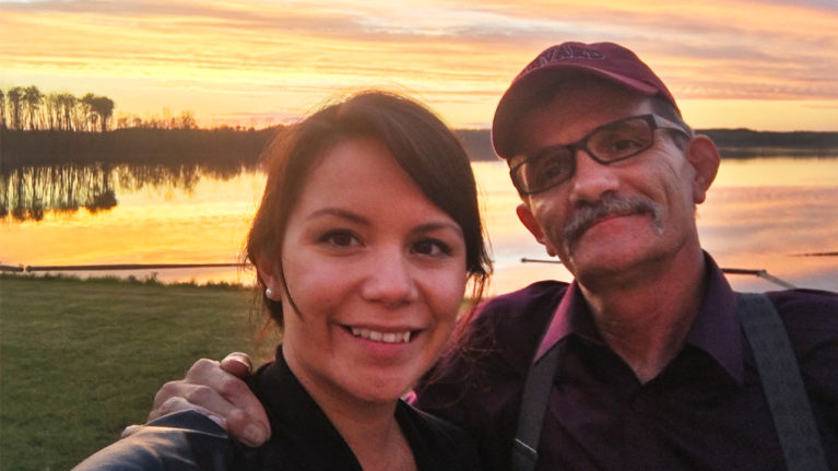 Young woman and her older father taking a selfie by a lake at sunset