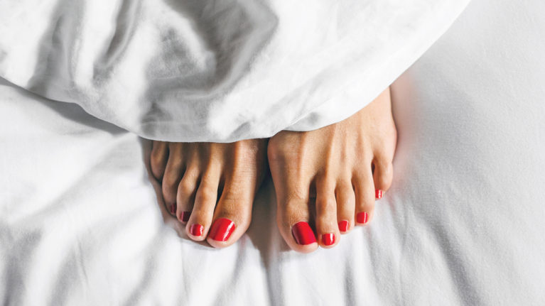 Feet with painted toenails peeking out from under a white bedsheet