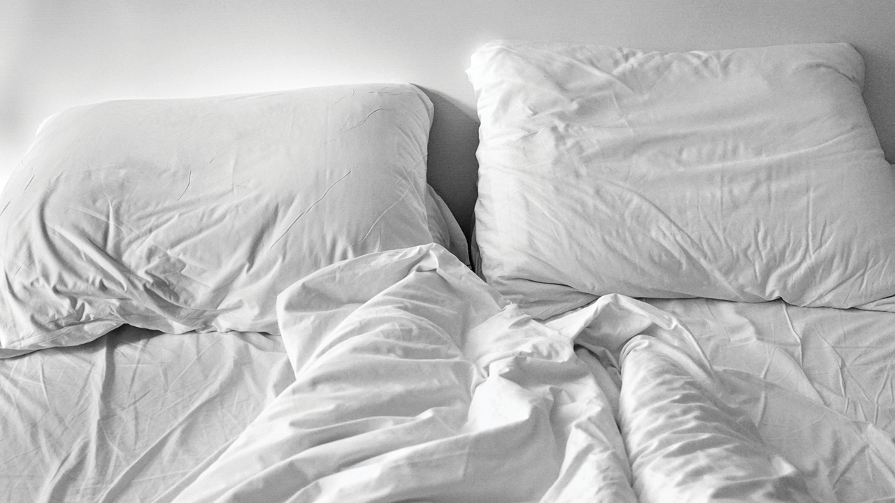empty bed with rumpled sheets