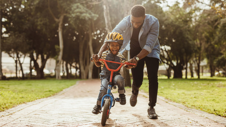 Dad teaching child to ride a bike