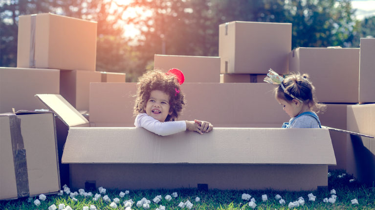 two siblings playing in cardboard boxes in the back yard