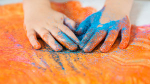 Kid's hands playing with orange paint and blue glitter