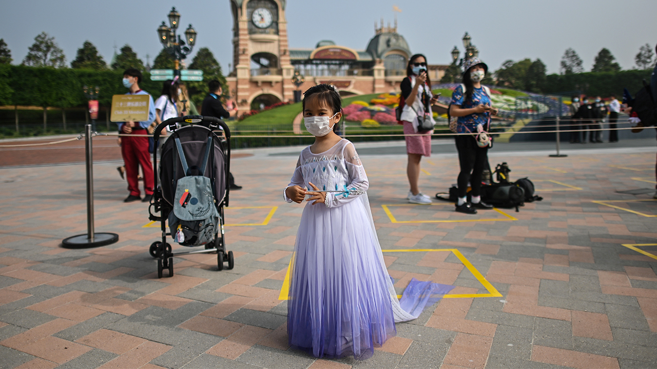 A girl wearing a face mask waits to enter the Disneyland amusement park in Shanghai on May 11, 2020. - Disneyland Shanghai reopened on May 11 to the public after being closed since January due to the COVID-19 coronavirus outbreak.