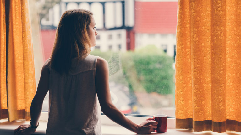 woman looking out the window of her house looking worried