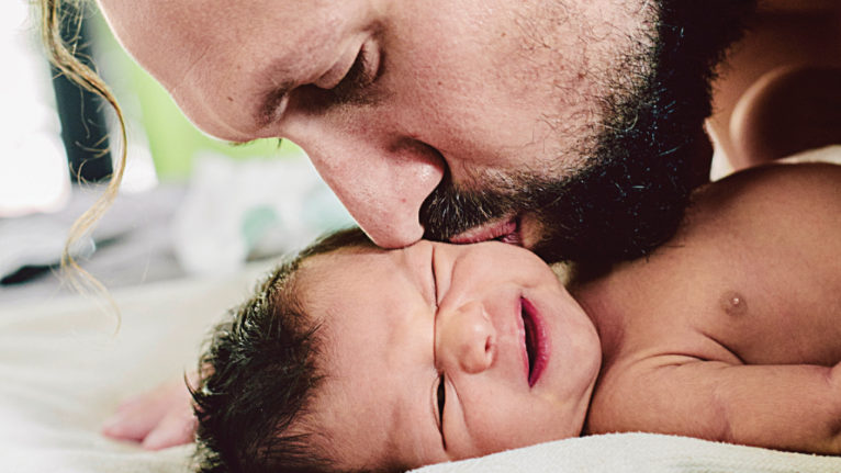 Kissing baby's cheek after dad struggling to bond with baby