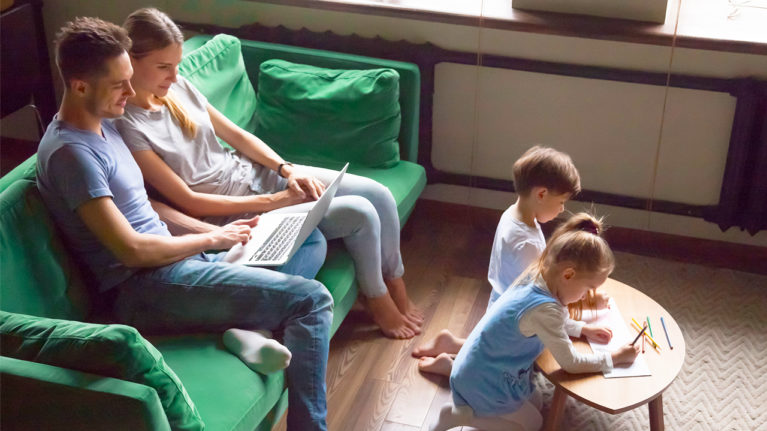 parents lounging on the couch while children colour on the coffee table