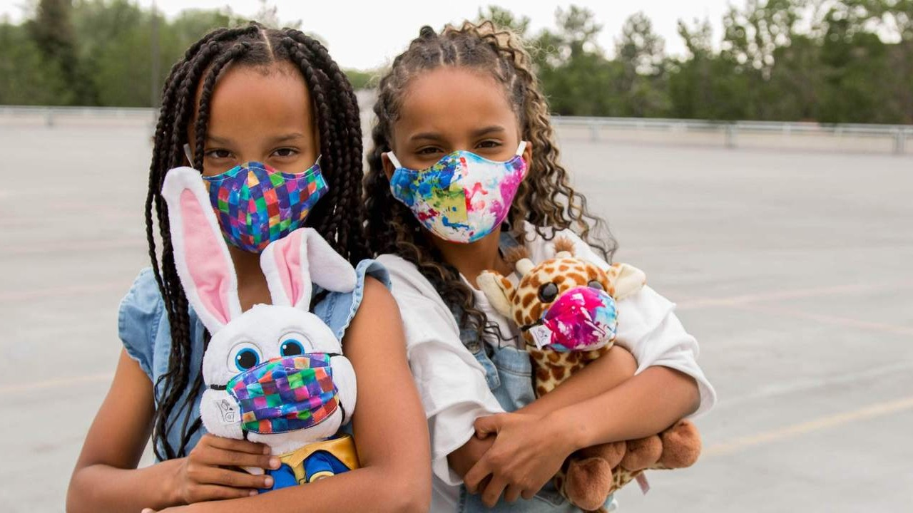 two young girls with stuffies wearing matching face masks