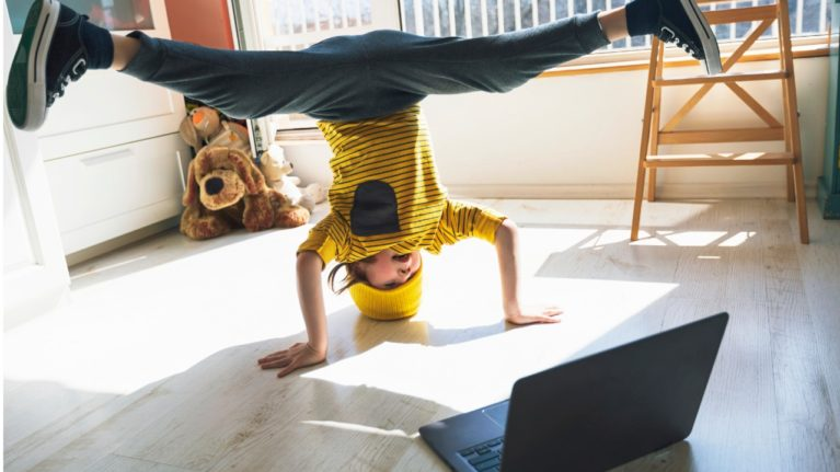 kid doing a headstand in front of a laptop