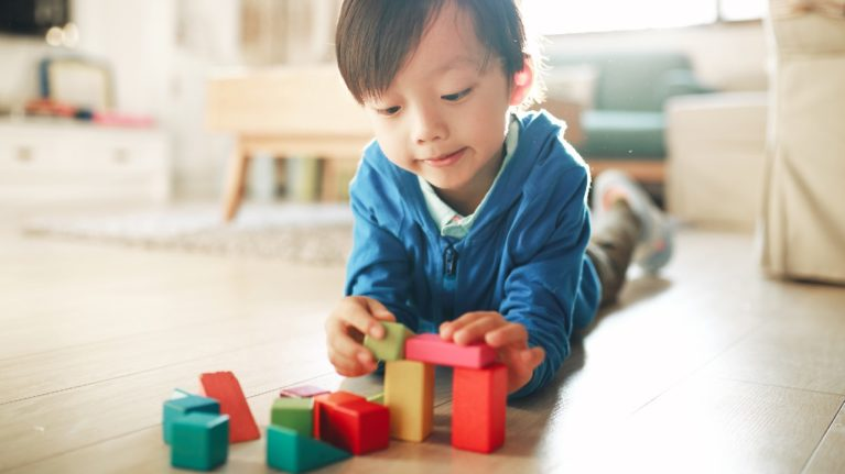 young boy playing with blocks diverse toys