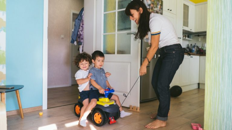 babysitter pulling kids in a toy car