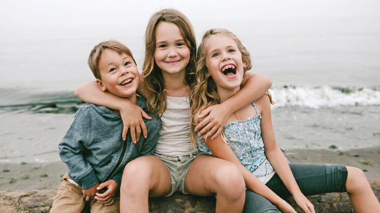 three kids sitting by the water together hugging and laughing