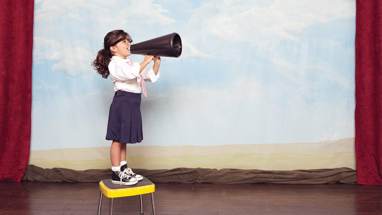 kid standing on a stool on a stage talking into a megaphone