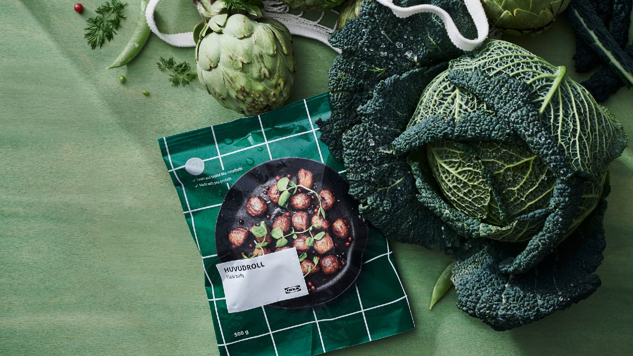lifestyle shot of packaged meatballs on green background surrounded by vegetables