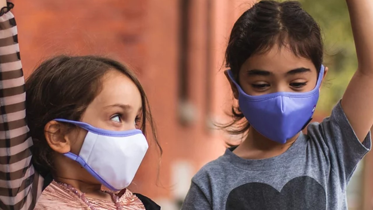 two young girls playing together while wearing masks