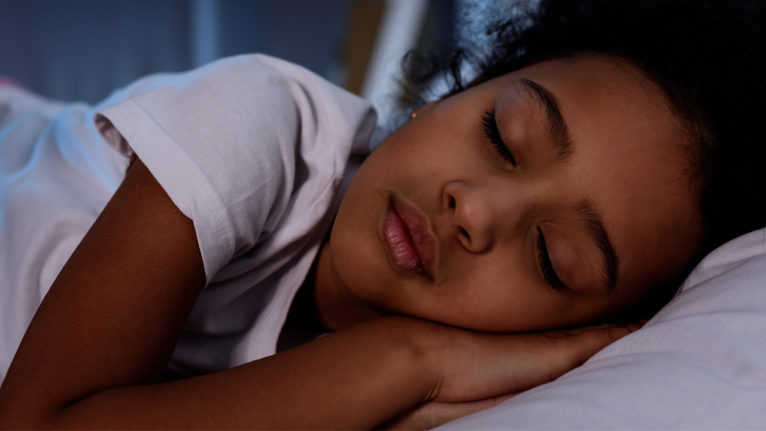 photo of Young girl sleeping in bed for a piece on sleep problems in children