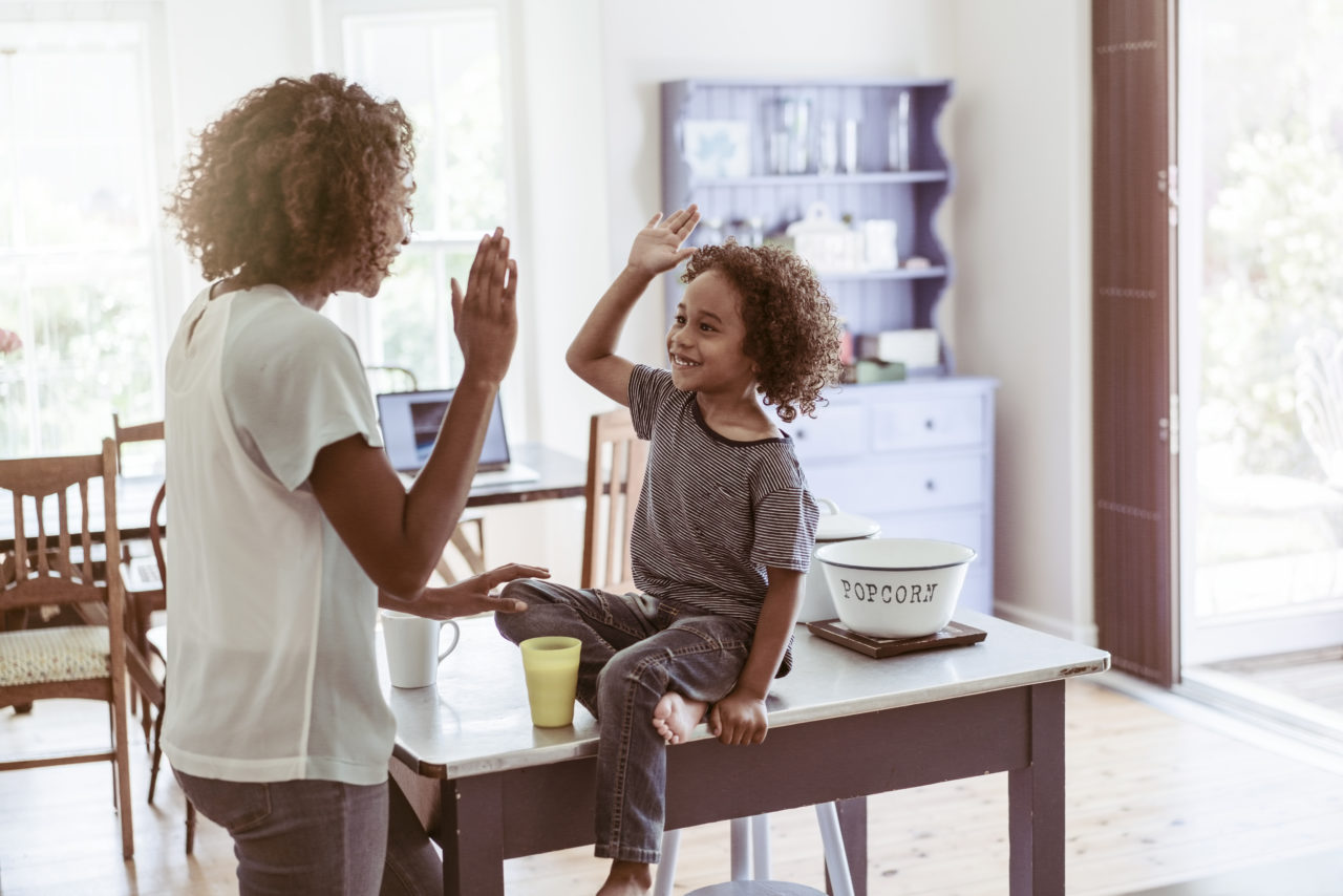 Happy little boy giving high-five to mother at home. Young woman is standing while son sitting on table. They are wearing casuals.