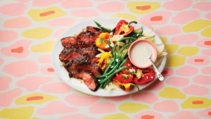 plate with grilled flank steak, green beans, peppers and a yogurt dipping sauce on a patterned table cloth