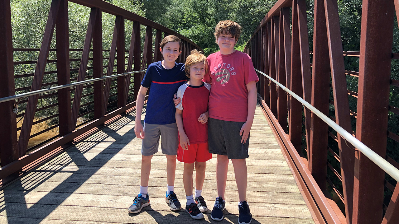 Three kids posing for a picture on a walking bridge in a park