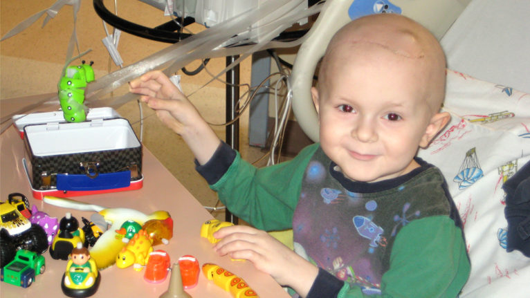 a young child with cancer playing with toys on a hospital bed