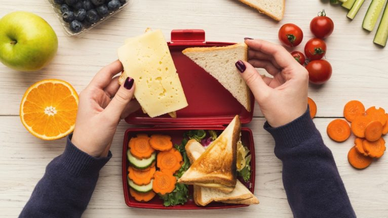 hands assembling healthy school lunches