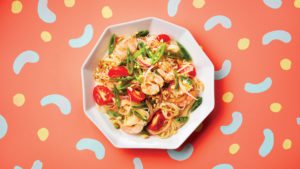 A plated dish of shrimp and vegetable noodle salad on a colourful backdrop
