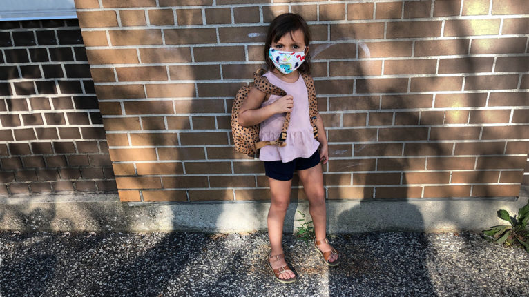 The author's daughter wearing a backpack and a face mask