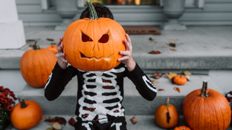 A young boy sitting on the porch with his carved pumpkin at halloween
