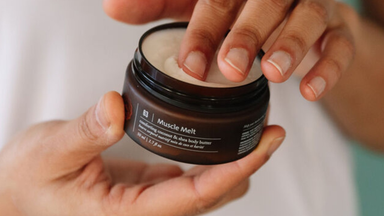 hands dipping into jar of saje muscle melt body butter