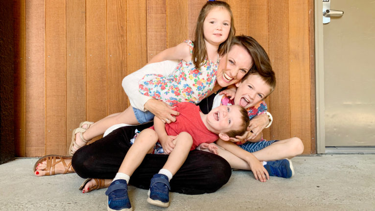 Author Susie Allison of Busy Toddler plays on the ground with her children