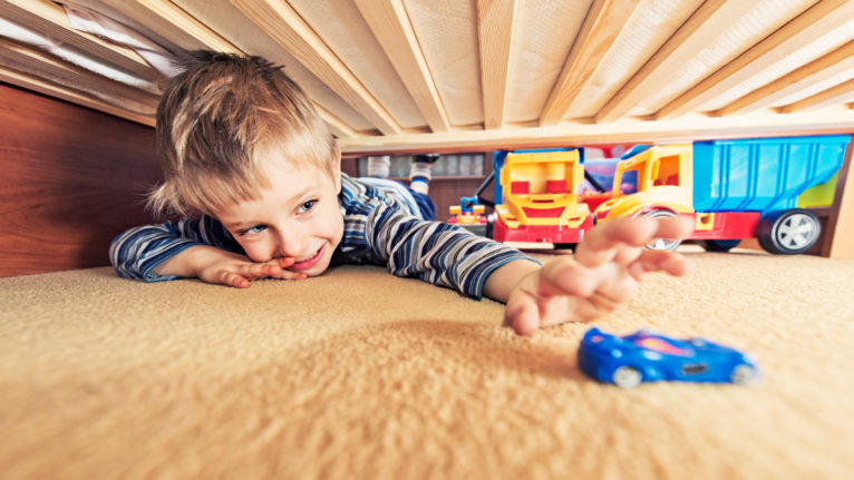 Child reaches under bed to grab toy before any kids organization methods have been put in place