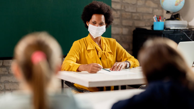 Teacher and student wearing masks sitting at desks, smiling at each other