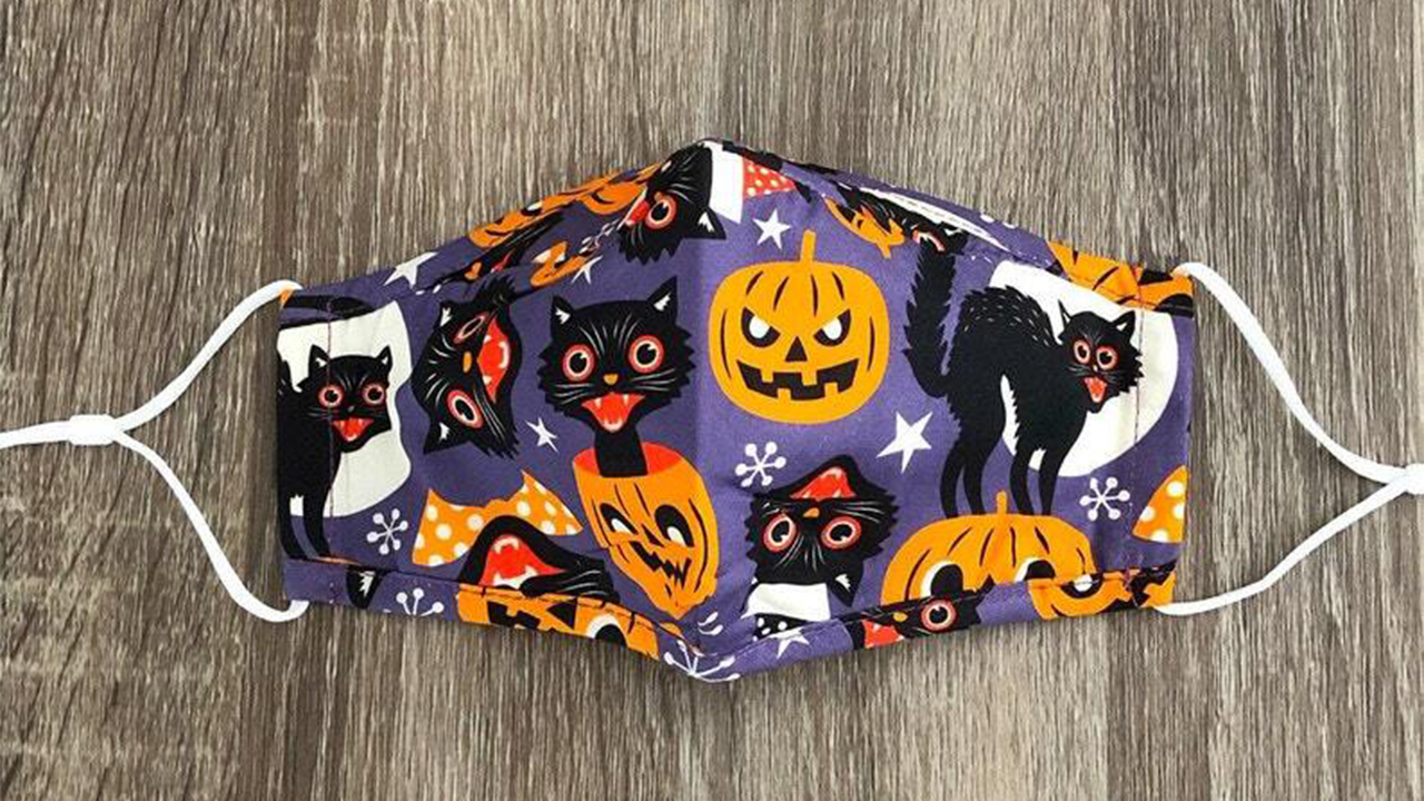 a face mask with pumpkin and black cat decals
