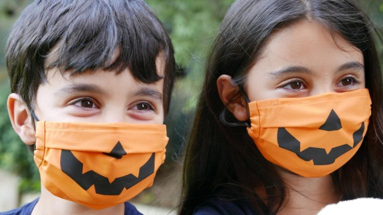 two young kids wearing pumpkin-style face masks