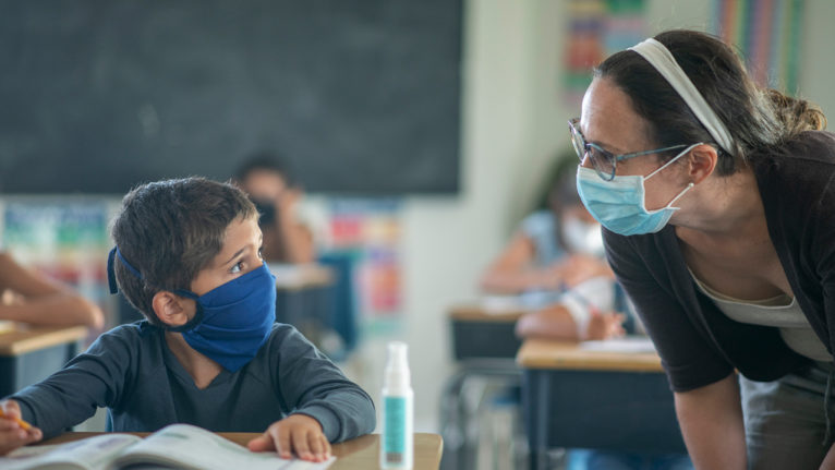 Teacher wearing a mask bending down to help a kid who is also wearing a mask