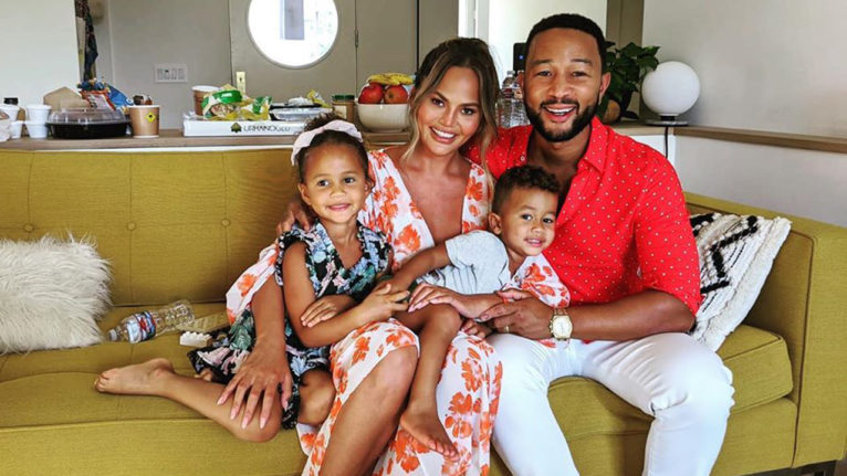 Chrissy Teigen and John Legend posing on the couch with their two children