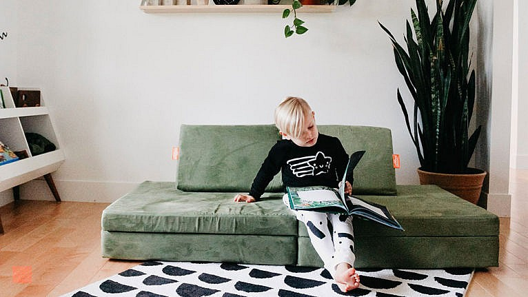 Photo of kid lounging on a kids' couch reading a picture book