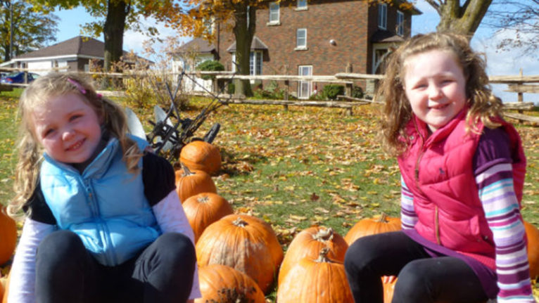 Photo of two young kids taking a picture at a pumpkin patch